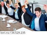 Geschäftsleute heben Hände zur Motivation in einem Meeting im Büro. Стоковое фото, фотограф Zoonar.com/Robert Kneschke / age Fotostock / Фотобанк Лори