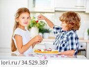 Zwei Kinder in der Küche backen zusammen einen Obstkuchen mit Johannisbeeren. Стоковое фото, фотограф Zoonar.com/Robert Kneschke / age Fotostock / Фотобанк Лори