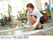 Frau arbeitet in Startup Business mit Unterlagen auf dem Boden vom... Стоковое фото, фотограф Zoonar.com/Robert Kneschke / age Fotostock / Фотобанк Лори