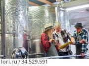 Gruppe Arbeiter mit Checkliste in Brauerei oder Weinkellerei vor ... Стоковое фото, фотограф Zoonar.com/Robert Kneschke / age Fotostock / Фотобанк Лори
