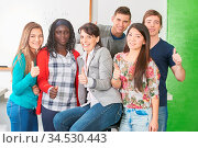 Schüler und Lehrer als Gruppe halten die Daumen hoch in der Schule. Стоковое фото, фотограф Zoonar.com/Robert Kneschke / age Fotostock / Фотобанк Лори