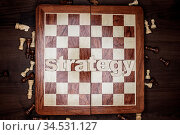Word strategy and chessmen on the brown wooden background. Стоковое фото, фотограф Zoonar.com/Ruslan Ropat / age Fotostock / Фотобанк Лори