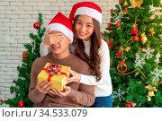 Beautiful asian girl give surprise christmas gift to her boyfriend... Стоковое фото, фотограф Zoonar.com/Vichaya Kiatying-Angsulee / easy Fotostock / Фотобанк Лори