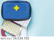 First aid kit on blue background with copy space, medications, pain relievers, antibiotics, vitamins, antidepressants, antivirals, tourniquet for stopping bleeding, bandage for assisting in accidents. Стоковое фото, фотограф Светлана Евграфова / Фотобанк Лори