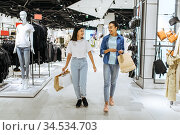 Girlfriends with bags walks in clothing store. Стоковое фото, фотограф Tryapitsyn Sergiy / Фотобанк Лори