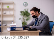 Young male employee in the office during pandemic disease. Стоковое фото, фотограф Elnur / Фотобанк Лори