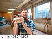 Arbeiter oder Schreiner Lehrling mit Bart trägt Balken aus Holz in... Стоковое фото, фотограф Zoonar.com/Robert Kneschke / age Fotostock / Фотобанк Лори