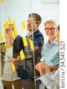 Geschäftsleute schreiben Notizen auf Zettel an eine Glaswand. Стоковое фото, фотограф Zoonar.com/Robert Kneschke / age Fotostock / Фотобанк Лори