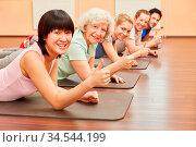 Glückliche Gruppe mit Seniorin im Yoga Kurs hält die Daumen hoch. Стоковое фото, фотограф Zoonar.com/Robert Kneschke / age Fotostock / Фотобанк Лори