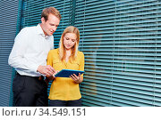 Zwei Studenten schauen draußen zusammen auf einen Tablet PC. Стоковое фото, фотограф Zoonar.com/Robert Kneschke / age Fotostock / Фотобанк Лори