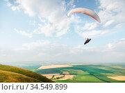 A white-orange paraglider flies over the mountainous terrain. Стоковое фото, фотограф Zoonar.com/Ian Iankovskii / easy Fotostock / Фотобанк Лори