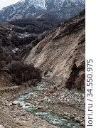 A fast mountain river flows along stony slopes of the gray Caucasus... Стоковое фото, фотограф Zoonar.com/Ian Iankovskii / easy Fotostock / Фотобанк Лори