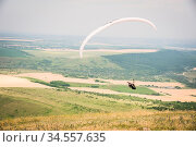 White orange paraglide with a paraglider in a cocoon against the background... Стоковое фото, фотограф Zoonar.com/Ian Iankovskii / easy Fotostock / Фотобанк Лори