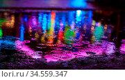 Reflektion bunter Lichter vom Jahrmarkt in einer Pfütze bei Regen. Стоковое фото, фотограф Zoonar.com/Robert Kneschke / age Fotostock / Фотобанк Лори