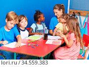 Zufriedene Gruppe Kinder beim Zeichnen zusammen in der Vorschule ... Стоковое фото, фотограф Zoonar.com/Robert Kneschke / age Fotostock / Фотобанк Лори