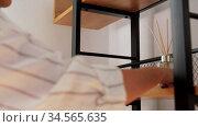 woman placing aroma reed diffuser to shelf home. Стоковое видео, видеограф Syda Productions / Фотобанк Лори