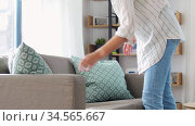 woman arranging cushions at home. Стоковое видео, видеограф Syda Productions / Фотобанк Лори