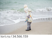 Cute little girl playing on the sandy beach. Happy child wearing warm floral print jacket, pom pom hat and scarf playing outdoors on fall, winter or spring day. Стоковое фото, фотограф Nataliia Zhekova / Фотобанк Лори