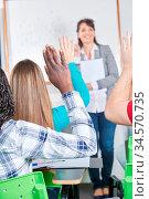 Schüler melden sich mit der Hand im Unterricht in der Schule. Стоковое фото, фотограф Zoonar.com/Robert Kneschke / age Fotostock / Фотобанк Лори