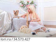 Luxurious blonde woman in a white dress with a dog pekingese in front... Стоковое фото, фотограф Zoonar.com/Figurniy Sergey / age Fotostock / Фотобанк Лори