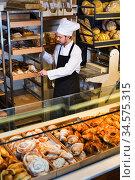 Man baker showing warm tasty croissant. Стоковое фото, фотограф Яков Филимонов / Фотобанк Лори