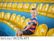 Child take own seat in the stadium or dolphinarium. Стоковое фото, фотограф Nataliia Zhekova / Фотобанк Лори