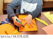 Child trace around a hand on paper with crayons. Стоковое фото, фотограф Nataliia Zhekova / Фотобанк Лори