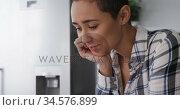 Woman using smartphone and smiling in kitchen. Стоковое видео, агентство Wavebreak Media / Фотобанк Лори