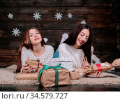 Two beautiful girls lie on the floor between the gifts for Christmas. Стоковое фото, фотограф Zoonar.com/Oleksii Hrecheniuk / age Fotostock / Фотобанк Лори