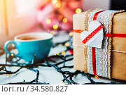 Gift is on the table, a garland in the background. Стоковое фото, фотограф Zoonar.com/Oleksii Hrecheniuk / age Fotostock / Фотобанк Лори