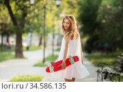 Portrait of lovely urban girl in white dress with a pink skateboard. Стоковое фото, фотограф Nataliia Zhekova / Фотобанк Лори