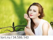 Lovely urban girl sitting on a bench in a city park. Стоковое фото, фотограф Nataliia Zhekova / Фотобанк Лори