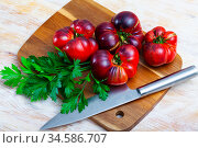 Brown tomatoes on wooden desk in home kitchen. Стоковое фото, фотограф Яков Филимонов / Фотобанк Лори
