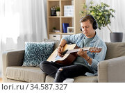man in headphones playing guitar at home. Стоковое фото, фотограф Syda Productions / Фотобанк Лори