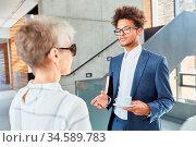 Afrikanischer Business Mann und blinde Kollegin beim Smalltalk in... Стоковое фото, фотограф Zoonar.com/Robert Kneschke / age Fotostock / Фотобанк Лори