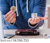 Young man mining bitcoins at home. Стоковое фото, фотограф Elnur / Фотобанк Лори