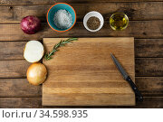 View of a wooden cutting board and knife with onion and seasonings arranged on a on a textured woode. Стоковое фото, агентство Wavebreak Media / Фотобанк Лори