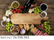View of a wooden cutting board with bread, cheese, sausage, fruits and wine on a wooden surface. Стоковое фото, агентство Wavebreak Media / Фотобанк Лори