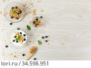 View of three bowls with muesli, nuts, blueberries and yoghurt on white wooden surface. Стоковое фото, агентство Wavebreak Media / Фотобанк Лори