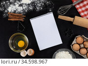 View of an empty notebook page with ingredients prepared for baking cookies, arranged on a plain bla. Стоковое фото, агентство Wavebreak Media / Фотобанк Лори