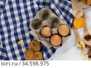 View of cookies, spoons with dried fruits and eggs on white wooden surface with tablecloth. Стоковое фото, агентство Wavebreak Media / Фотобанк Лори