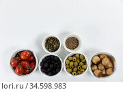 View of a six bowls with fresh tomatoes, olives, nuts and seasoning on plain white surface. Стоковое фото, агентство Wavebreak Media / Фотобанк Лори
