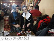 Two young Turkish girls drink tea and smoke a hookah at a café in... (2005 год). Редакционное фото, фотограф Andre Maslennikov / age Fotostock / Фотобанк Лори