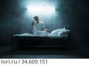 Psycho man sitting in bed, dark room on background. Стоковое фото, фотограф Tryapitsyn Sergiy / Фотобанк Лори