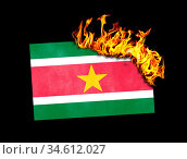Flag burning - concept of war or crisis - Suriname. Стоковое фото, фотограф Zoonar.com/Micha Klootwijk / age Fotostock / Фотобанк Лори