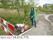 Woman with street work machine constructing bike lane to reduce environmental... Редакционное фото, фотограф Egerland Productions / age Fotostock / Фотобанк Лори