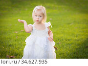 Beautiful Adorable Little Girl Wearing White Dress In A Grass Field. Стоковое фото, фотограф Zoonar.com/Andy Dean Photography / age Fotostock / Фотобанк Лори
