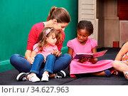 Afrikanisches Mädches liest Buch im Kindergarten neben der Kindergärtnerin. Стоковое фото, фотограф Zoonar.com/Robert Kneschke / age Fotostock / Фотобанк Лори