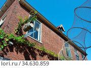 Fischreuse vor einer Backsteinfassade. Friesland, Niederlande. Стоковое фото, фотограф Zoonar.com/Gabriele Sitnik-Schmach / easy Fotostock / Фотобанк Лори