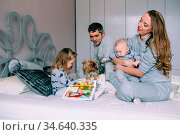 Portrait of happy young family playing on bed in the bedroom. Стоковое фото, фотограф Zoonar.com/Oleksii Hrecheniuk / age Fotostock / Фотобанк Лори